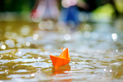 Orange paper boat with a white flag